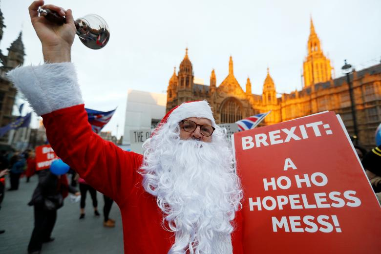 A man in a Santa Claus costume holds an anti-Brexit placard and rings a bell outside the Houses of Parliament in London, December 10, 2018.