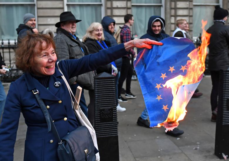 Pro-Brexit supporters burn an EU flag during a UKIP demonstration in central London, December 9, 2018.