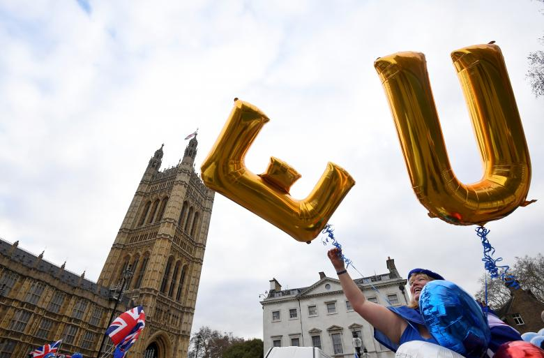 An anti-Brexit protester holds balloons opposite the Houses of Parliament in London, December 10, 2018.