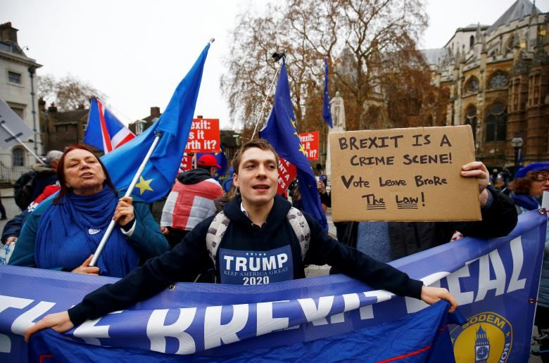 A Trump supporter waves a flag amongst anti-Brexit demonstrators during a protest opposite the Houses of Parliament, London, December 4, 2018.