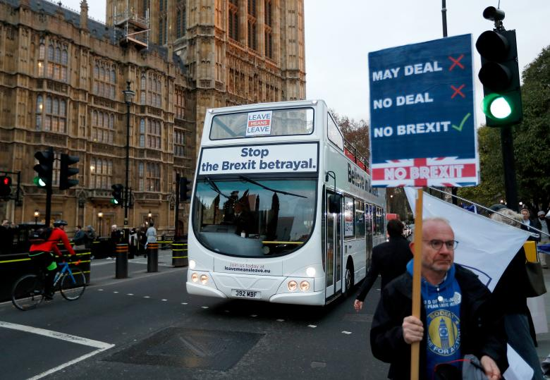 A bus with a pro-Brexit message passes an anti-Brexit demonstrator outside the Houses of Parliament in London, December 10, 2018.