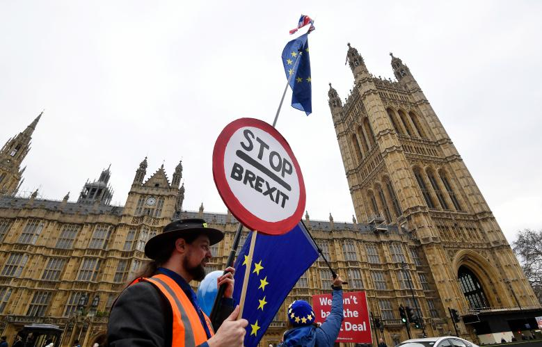 Anti-Brexit protesters wave flags and placards opposite the Houses of Parliament in London, December 10, 2018.