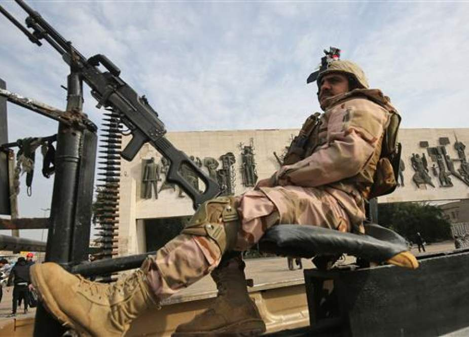 Iraqi soldier sits atop a military vehicle in central Baghdad