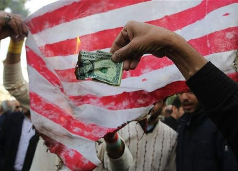 On the eve of renewed sanctions by Washington, Iranian protesters burn a dollar banknote and a US makeshift flag during a demonstration outside the former US embassy in the Iranian capital Tehran on November 4, 2018. (Photo by AFP)