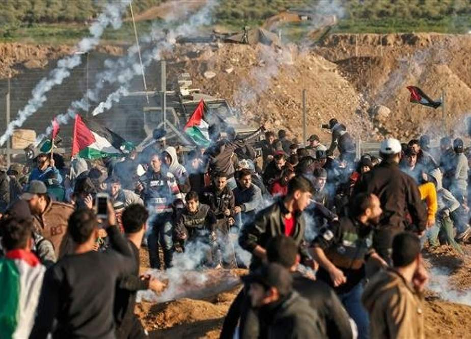 This picture taken on January 11, 2019, shows a view of clashes between Palestinians and Israeli forces across the fence, following a demonstration along the border between the Gaza Strip and the occupied territories, with tear gas fumes erupting amidst the protesters. (AFP)