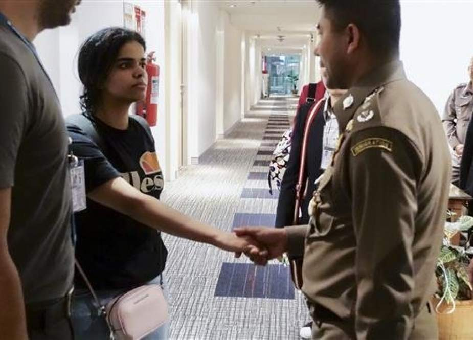 This handout picture taken and released by the Thai Immigration Bureau on January 7, 2019 shows 18-year-old Saudi girl Rahaf Mohammed al-Qanun (2nd-L) shaking hands with a Thai immigration officer at Suvarnabhumi international airport in Bangkok. (Photo by AFP)