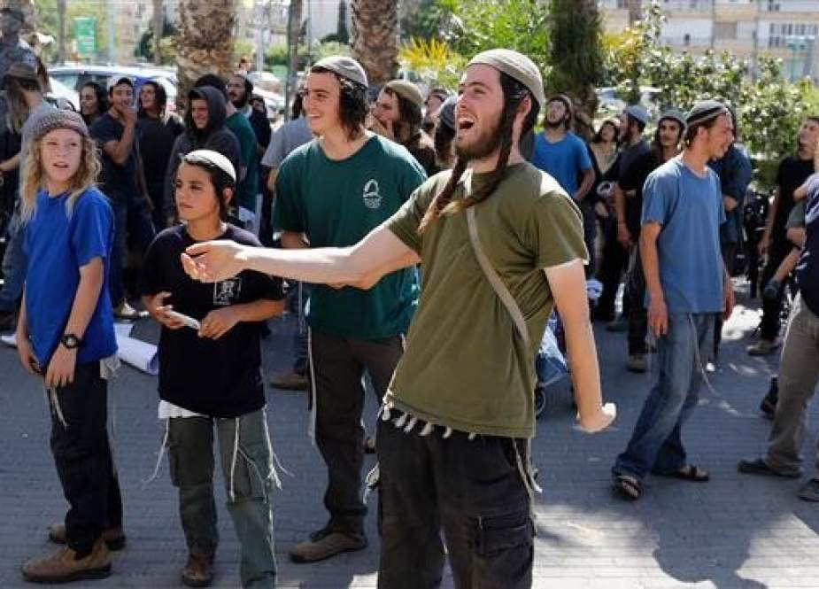 Extremist Israeli settlers and supporters of two young Jewish men suspected in an arson attack that killed a Palestinian toddler and his parents demonstrate outside of the Lod court on June 19, 2018. (Photo by AFP)