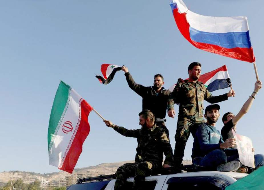 Syrians wave Iranian, Russian, and Syrian flags during a protest against US-led airstrikes in Damascus, Syria, on April 14, 2018. (Photo by Reuters)