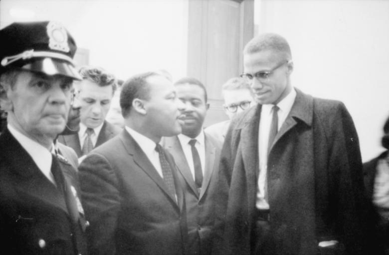 Martin Luther King Jr. and Malcolm X wait for a press conference to begin in an unknown location, March 26, 1964.