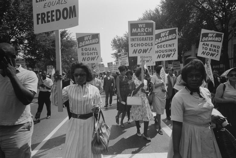 People carry signs for equal rights, integrated schools, decent housing and an end to bias during the civil rights March on Washington, August 28, 1963.