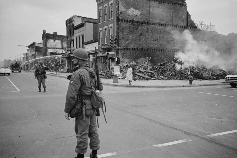 A soldier stands guard at 7th and N Street, N.W., Washington, with the ruins of buildings destroyed during the riots that followed the assassination of Martin Luther King Jr., April 8, 1968.
