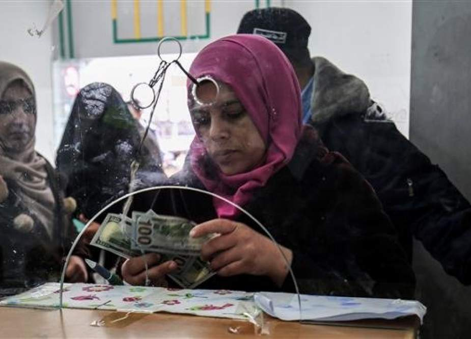 A Palestinian government employee receives a portion of her overdue salary at a post office in Rafah in the southern Gaza Strip on December 8, 2018. (Photo by AFP)