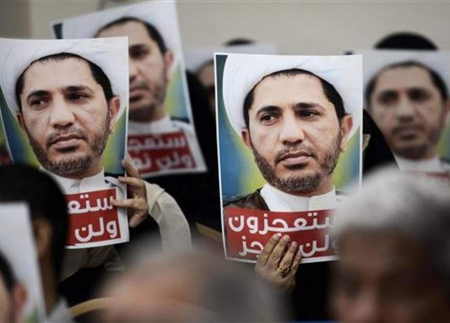 In this file photo, taken on May 29, 2016, Bahraini men are seen holding placards bearing the portrait of Sheikh Ali Salman, the head of the now-dissolved opposition movement al-Wefaq, during a protest against his arrest, at the al-Wefaq headquarter building, in the village of Zinj, on the outskirts of the capital, Manama. (By AFP)