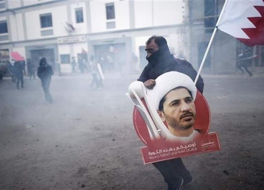 In this file photo, taken on February 13, 2015, a Bahraini protester carrying a placard showing Sheikh Ali Salman, is seen taking cover from tear gas during clashes with police, in Salman's home village of Bilad al-Qadeem, on the outskirts of the capital, Manama, Bahrain. (By AFP)