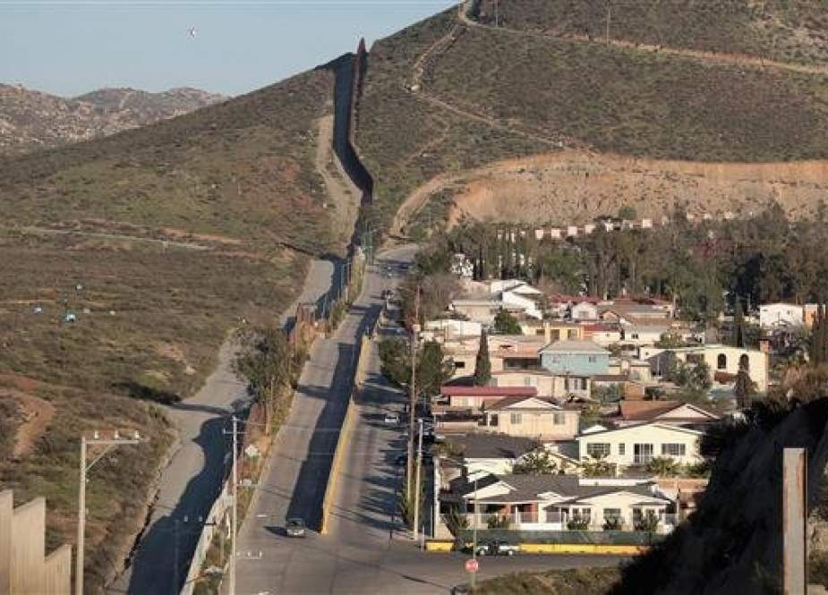 The border wall that separates the United States from Mexico runs along a neighborhood on January 27, 2019 in Tecate, Mexico. (Photo by AFP)