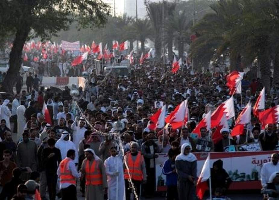Thousands of Bahraini anti-government protesters chant slogans as they wave national flags during a march in Diraz, Bahrain, January 17, 2014. (By AP)
