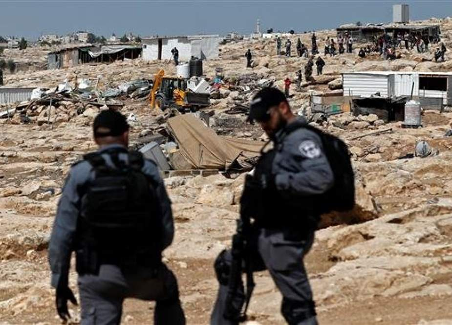 Israeli police officers secure a bulldozer demolishing structures in the Palestinian Bedouin village of Khan al-Ahmar east of Jerusalem al-Quds in the occupied West Bank on July 4, 2018. (Photo by AFP)