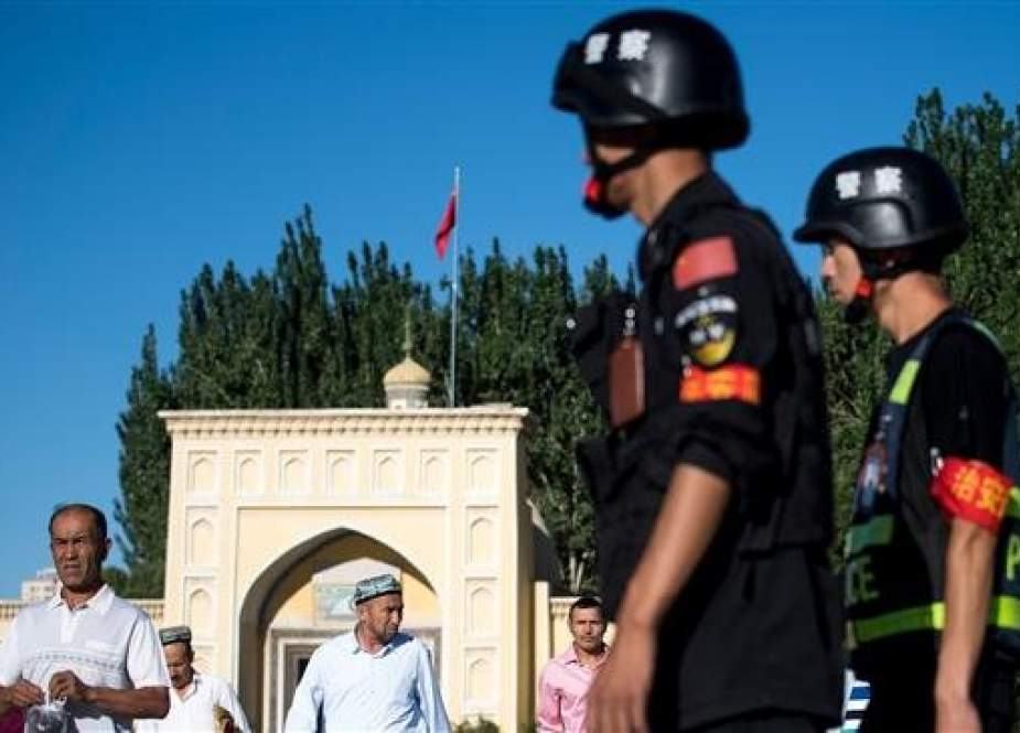 This picture taken on June 26, 2017 shows police patrolling as Muslims leave the Id Kah Mosque after the morning prayer on Eid al-Fitr in the old town of Kashgar in China