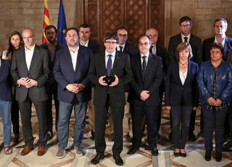 In this file photo, taken on October 1, 2017, then-Catalan president Carles Puigdemont (C) is seen talking to the media next to members of his government in Barcelona, following a referendum on independence for Catalonia banned by Madrid. (By AFP)