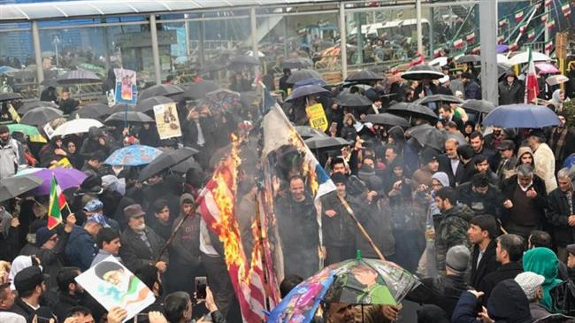 Iranian demonstrators burn a US flag during a rally commemorating the 1979 Islamic Revolution in Tehran, February 11, 2019.