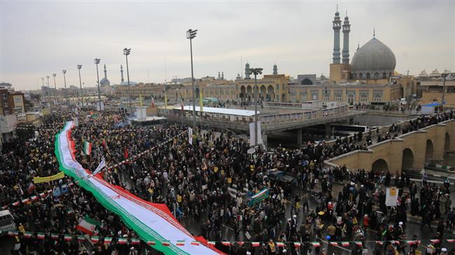 Iranians marking the anniversary of the Islamic Revolution carry a national flag in Qom, February 11, 2019.