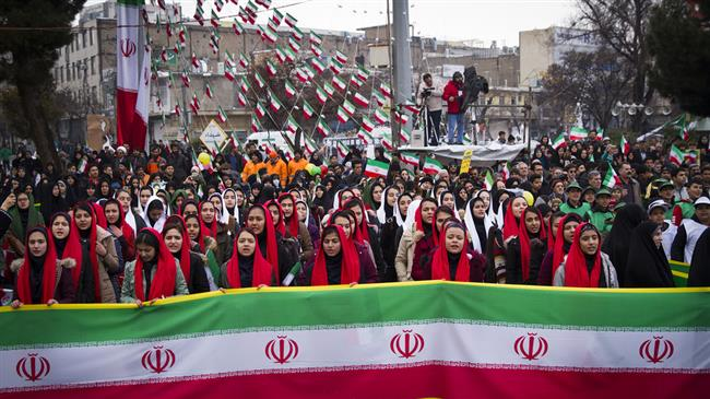 Iranian women in the city of Arak hold the national flag on the anniversary of the Islamic Revolution, February 11, 2019.