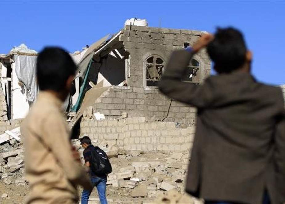 Yemenis look at a building destroyed in Saudi-led airstrikes in Yemen