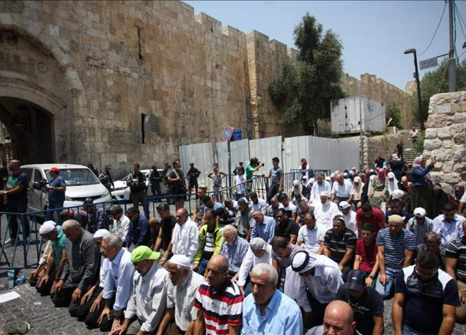 Palestinians pray outside the al-Aqsa Mosque compound in protest against the Israeli regime