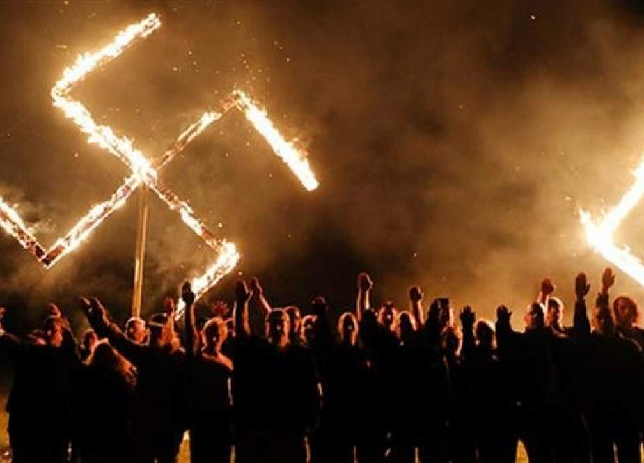 Members of the National Socialist Movement, one of the largest neo-Nazi groups in the US, hold a swastika burning after a rally on April 21, 2018 in Draketown, Georgia. (Photo by AFP)