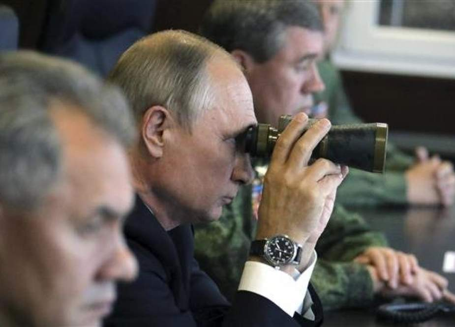 Russian President Vladimir Putin uses a pair of binoculars while watching the Zapad-2017 war games, held by Russian and Belarussian servicemen, at a military training ground in the Leningrad region, Russia on September 18, 2017. (Photo by Reuters)