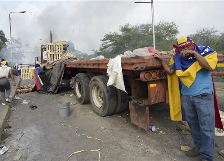 Demonstrators throw stones after a truck with humanitarian aid was set on fire at the Francisco de Paula Santander international bridge Bridge linking Cucuta, Colombia, and Urena, Venezuela, during an attempt to cross over the border into Venezuela, on February 23, 2019. (AFP)