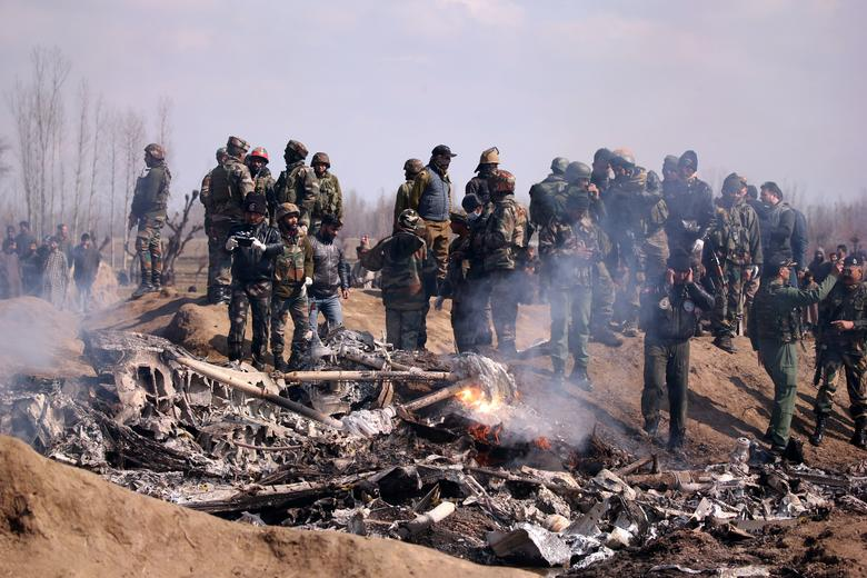 Indian soldiers stand next to the wreckage of Indian Air Force's helicopter after it crashed in Budgam district in Kashmir, February 27.