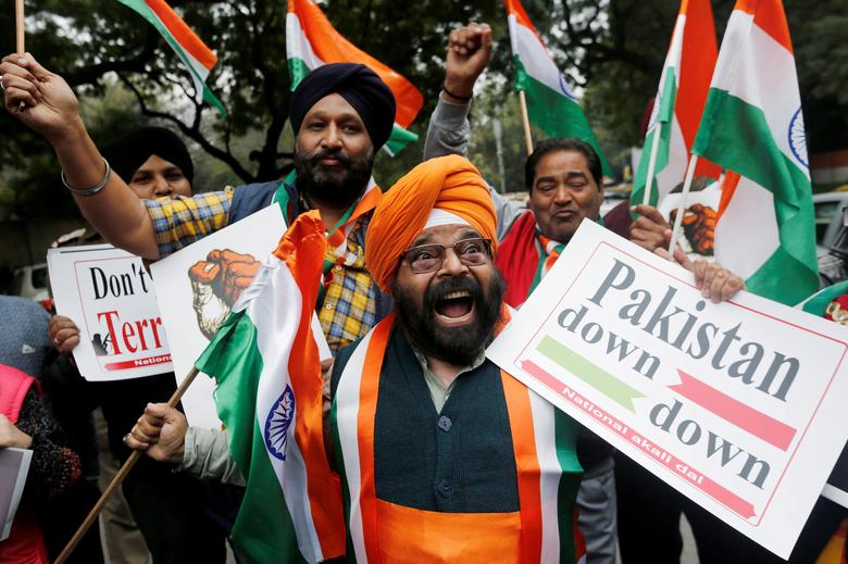 People hold national flags and placards as they celebrate after Indian authorities said their jets conducted airstrikes on militant camps in Pakistani territory, in New Delhi, India, February 26.