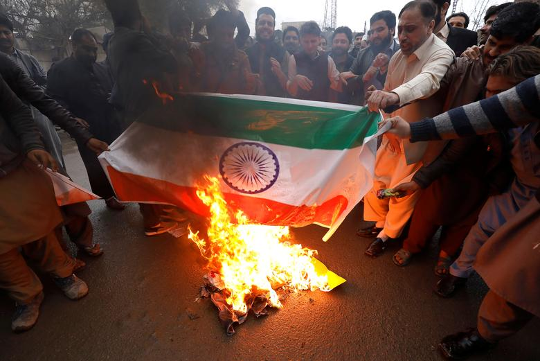 People burn a poster depicting India's flag against what they call airspace violation by the Indian military aircrafts, in a protest in Peshawar, Pakistan, February 26.