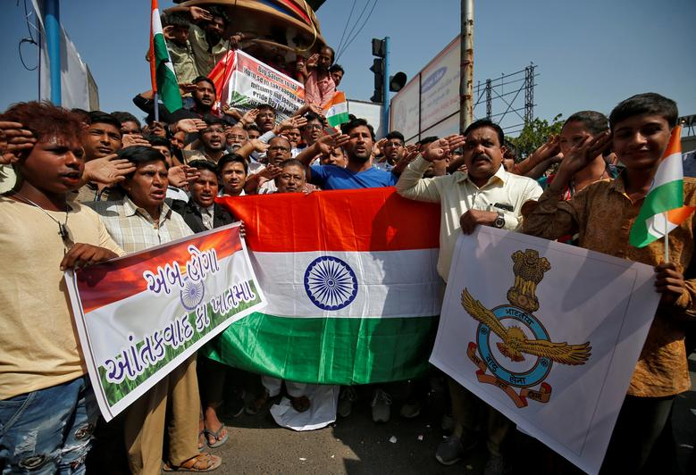 People hold national flags and an Indian Air Force flag as they salute to celebrate after Indian authorities said their jets conducted airstrikes on militant camps in Pakistani territory, in Ahmedabad, India, February 26.