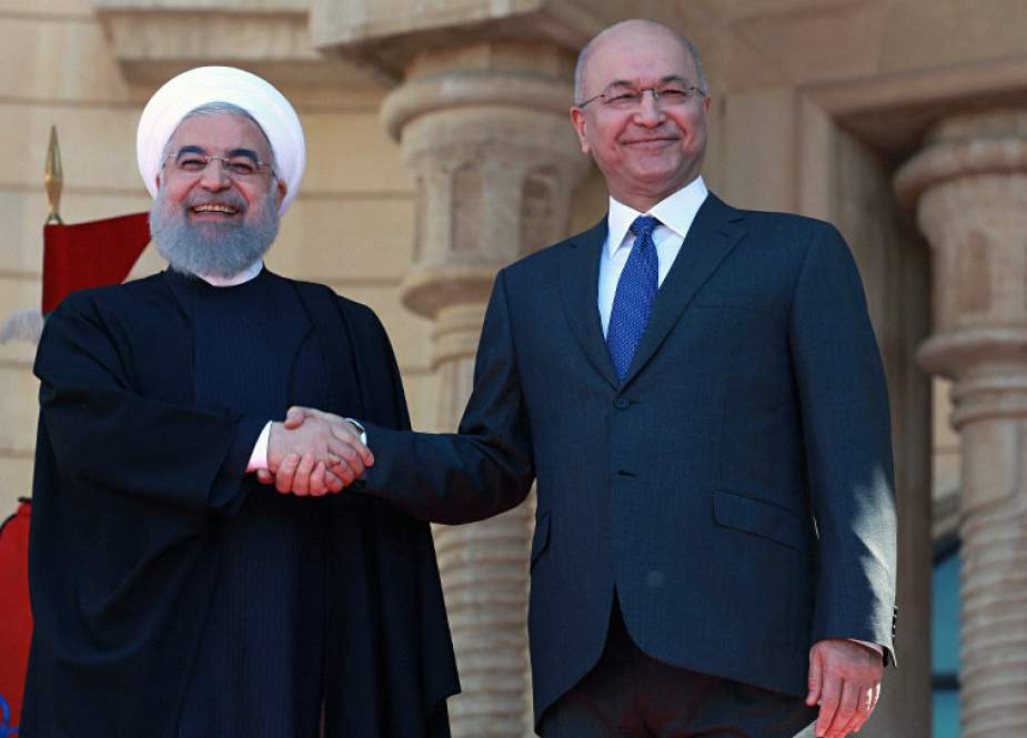Iranian President Hassan Rouhani (L) shakes hands with Iraqi President Barham Salih in Baghdad, Iraq, on March 11, 2019.
