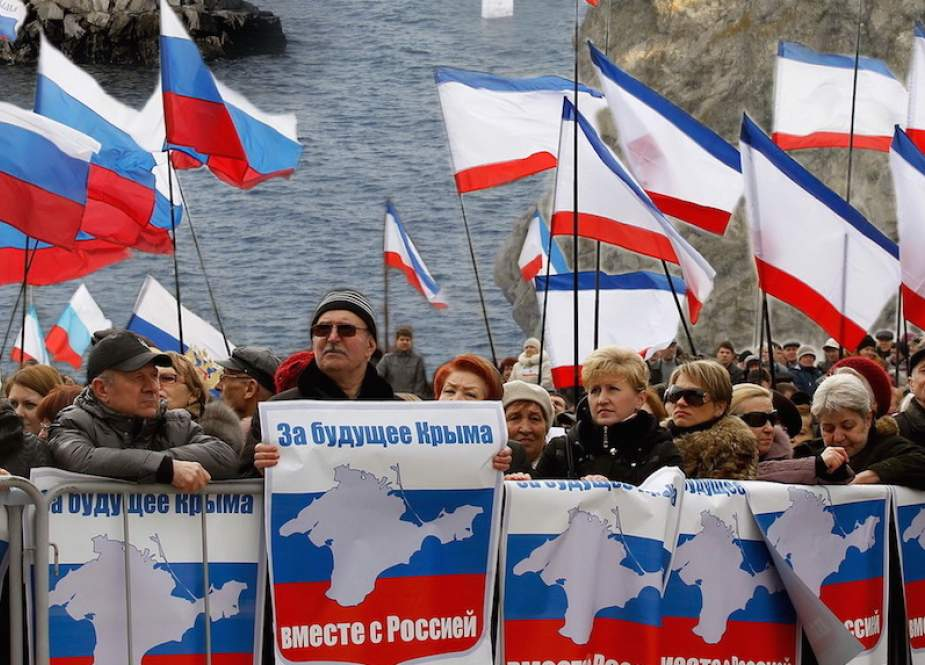 People carry flags during celebrations of the fifth anniversary of Crimea