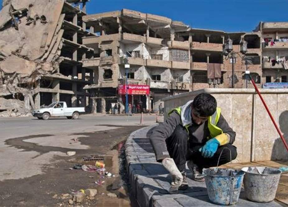 A worker repairs a pavement near a destroyed building in Daesh's former stronghold of Raqqah, in northern Syria, on February 19, 2019. (Photo by AFP)