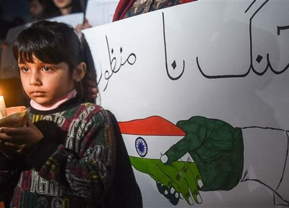 A Pakistani girl holds a light candle during a vigil for peace in Lahore on March 3, 2019. (Photo by AFP)