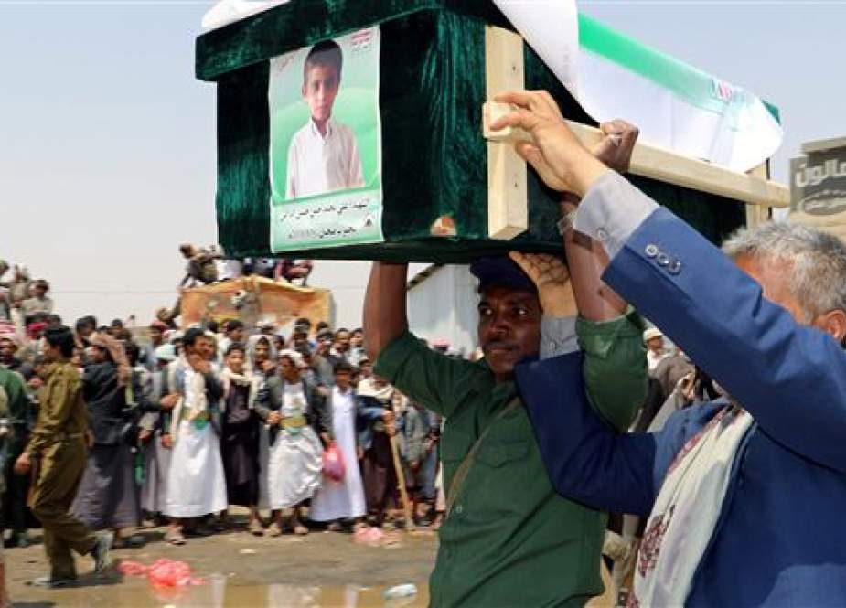 A mourner and a policeman carry the coffin of a boy during the funeral of people, mainly children, killed in a Saudi airstrike on a bus in northern Yemen, in Sa'ada, Yemen, on August 13, 2018.