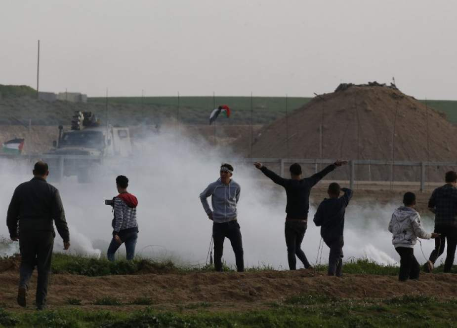 Palestinian demonstrators protest under tear gas canisters fired by Israeli forces during a demonstration near the fence along the border with the occupied territories, east of Gaza City, on February 8, 2019.