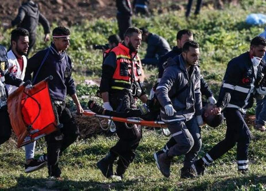 Palestinian paramedics carry a protester wounded by Israeli regime forces on a stretcher during protests, east of Gaza City, the Gaza Strip, on March 8, 2019. (Photo by AFP)