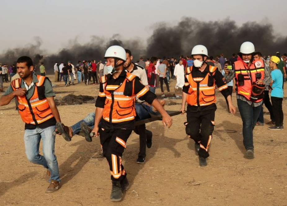 Palestinian paramedics carry away a protester injured during a demonstration along the Gaza Strip's border, east of Khan Yunis.jpg