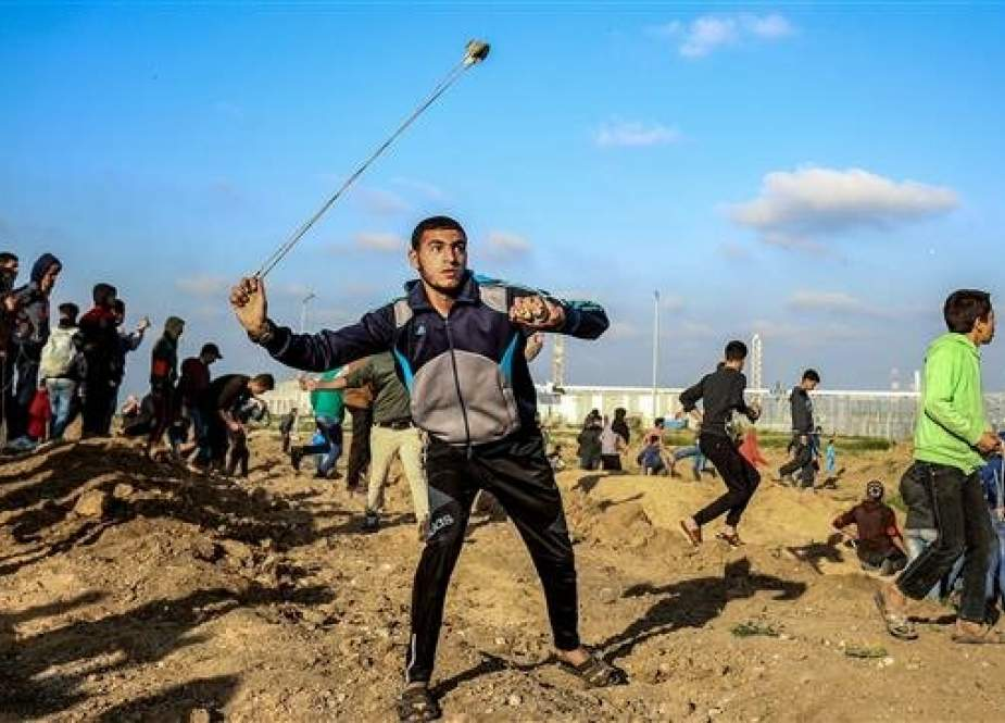 A Palestinian protester uses a slingshot to hurl objects during clashes with Israeli forces across the so-called border fence separating the Gaza Strip from the occupied Palestinian territories on March 22, 2019. (Photo by AFP)