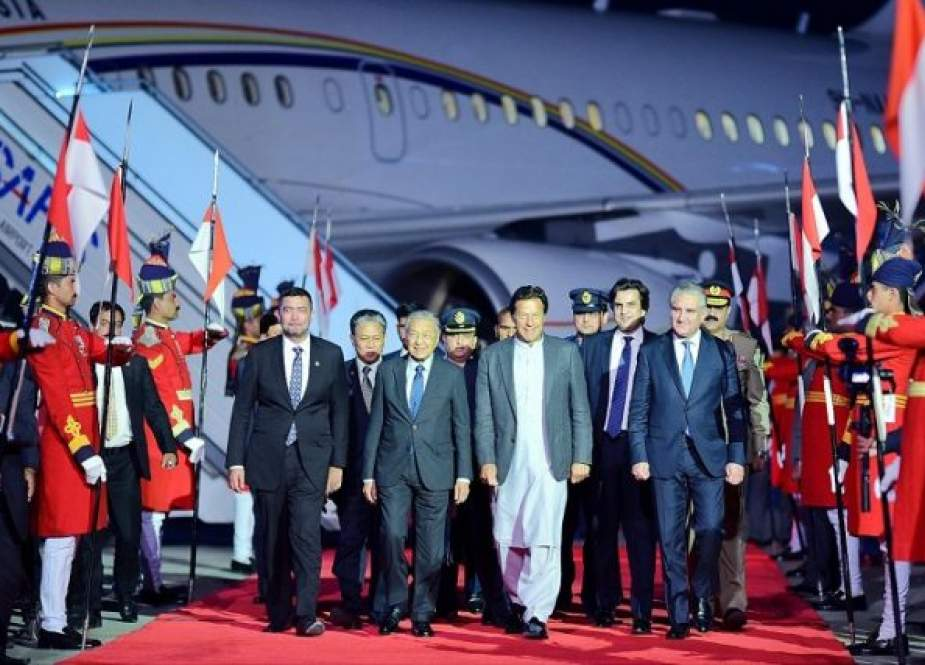 Malaysian Prime Minister Mahathir Mohamad, center, walks along with his Pakistani counterpart Imran Khan and other officials after arrival at Nur Khan Airbase Rawalpindi on March 21, 2019.