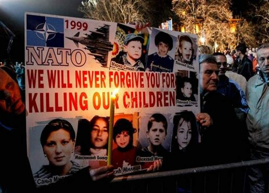 Serbian men hold a poster with pictures of victims of the 1999 NATO air campaign against Serbia and Montenegro, on March 24, 2019 in the town of Nis. Serbia marks on March 24, 2019 the 20th anniversary since NATO launched an air war to stop the crackdown on independence-seeking Kosovo by the regime of strongman Slobodan Milosevic. (AFP)