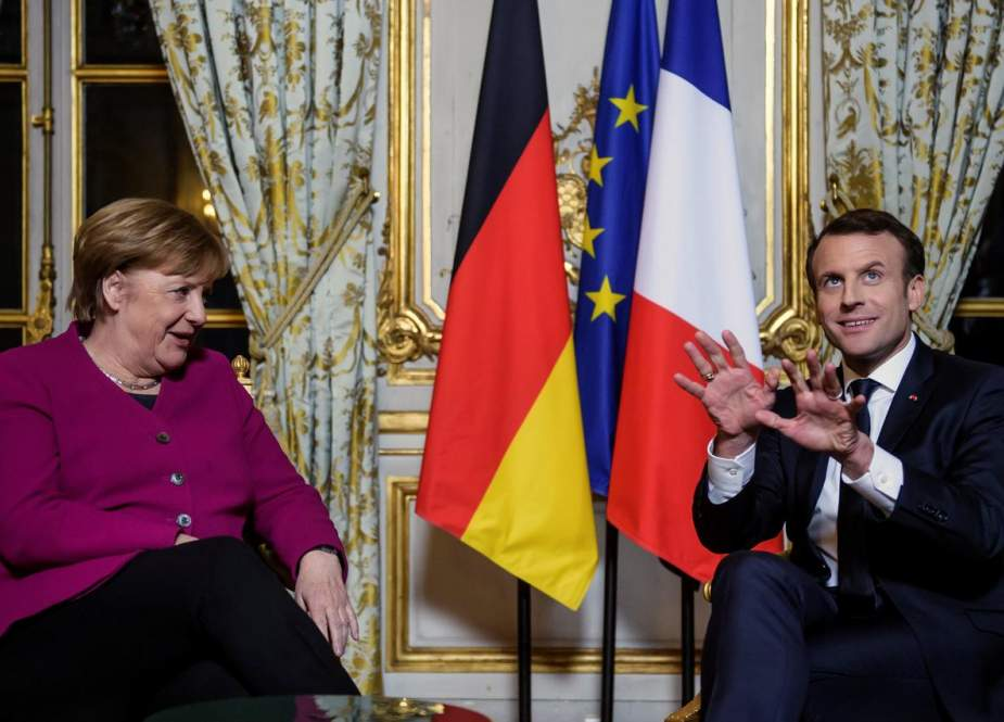 French President Emmanuel Macron speaks with German Chancellor Angela Merkel following their meeting at the Elysee Palace in Paris on March 26, 2019.