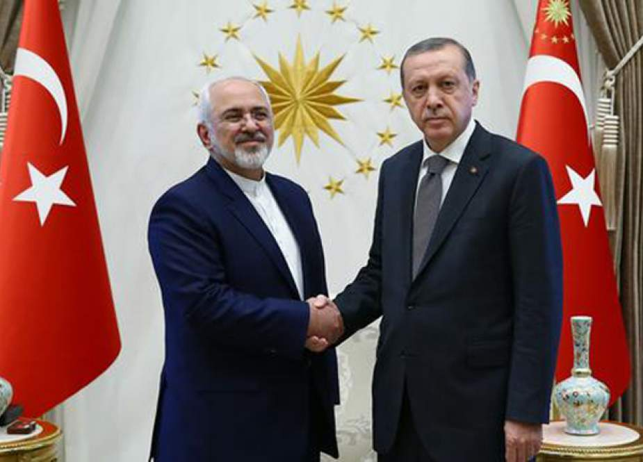 This picture taken on April 17, 2019 shows Turkish President Recep Tayyip Erdogan (R) shaking hands with Iranian Foreign Minister Mohammad Javad Zarif in Ankara, Turkey.