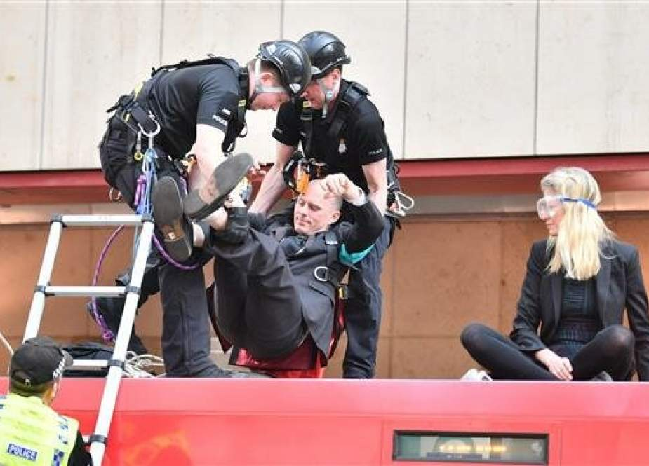Police remove climate change protestors who had glued themselves to the roof of a DLR train at Canary wharf station on the third day of an environmental protest by the Extinction Rebellion group, in London on April 17, 2019. (AFP photo)
