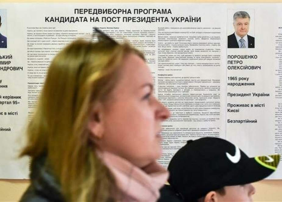 A voter walks past an information placard bearing portraits of the both candidates - President Petro Poroshenko and comedian Volodymyr Zelensky - at a polling station during the second round of Ukraine